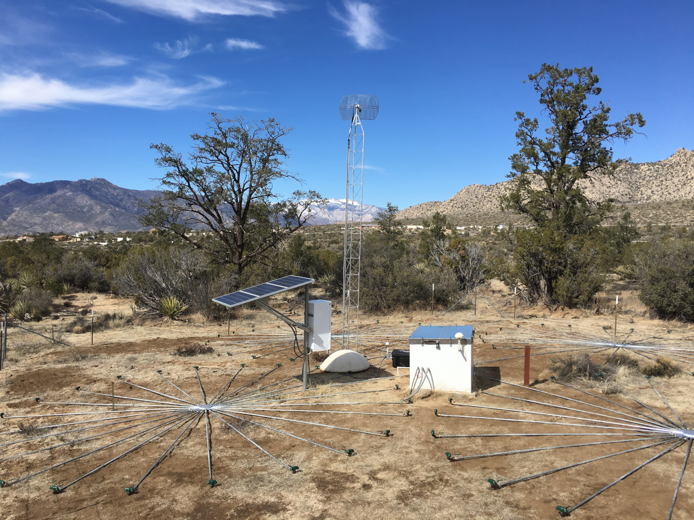 A box connected to array in bright sunshine with solar panel nearby. Tower is shown in background. Ground has dirt but no grass and looks like a desert.